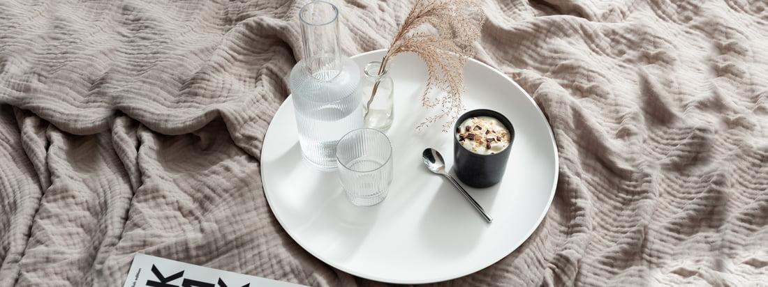 Den hvide Corian Bakke fra yunic er ideel som bakke til kopper og glas, ligesom Ripple-karaffen fra ferm Living. (Copyright: Felix Sodomann - Wohnglück Hamborg)