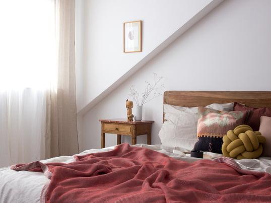 Pepper fra heimatbaum.com viser os, hvordan du designer dit soveværelse med tæppet af Muuto og knude puder af House Stockholm i røde og jordfarver.